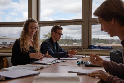 Students sitting at a table inside the library